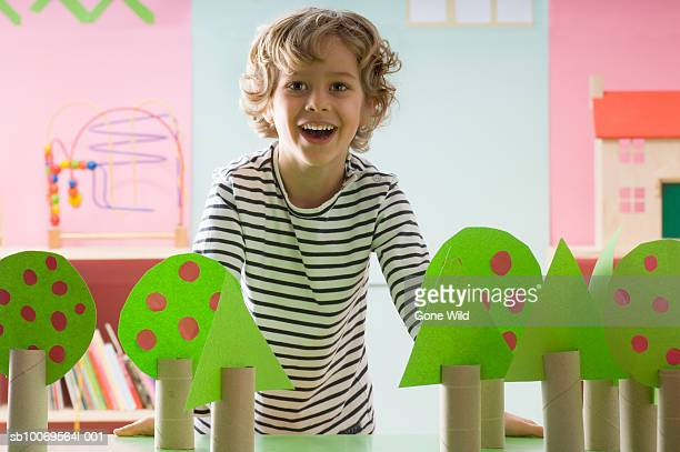 boy (4-5) behind cardboard trees in classroom, portrait - toilet paper tree stock pictures, royalty-free photos & images