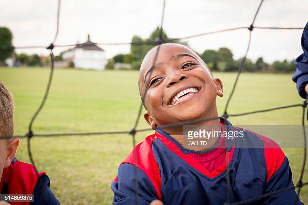 Boy behind football goal smiling