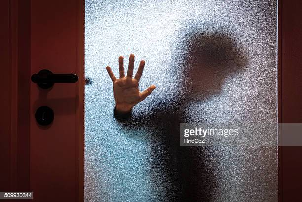 boy behind glass door - violence stock photos and pictures