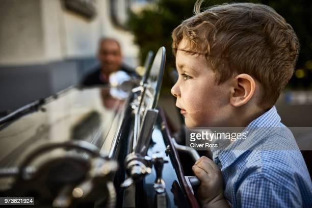 boy behind window in a vintage car - starren stock-fotos und bilder