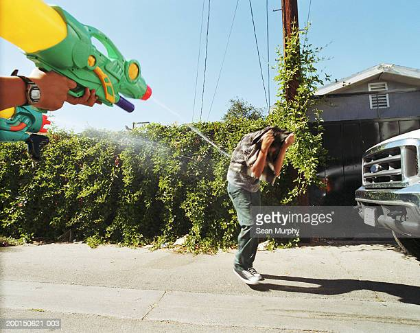 boy (13-15) being sprayed by friends with water guns - wet jeans stock photos and pictures