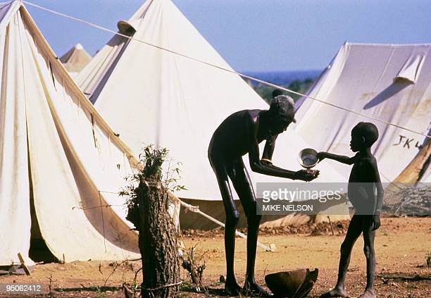 A boy belonging to Mundari displaced ethnic group gives some water in September 1986 to an old starving man in a UNHCR refugee camp outside Juba the...