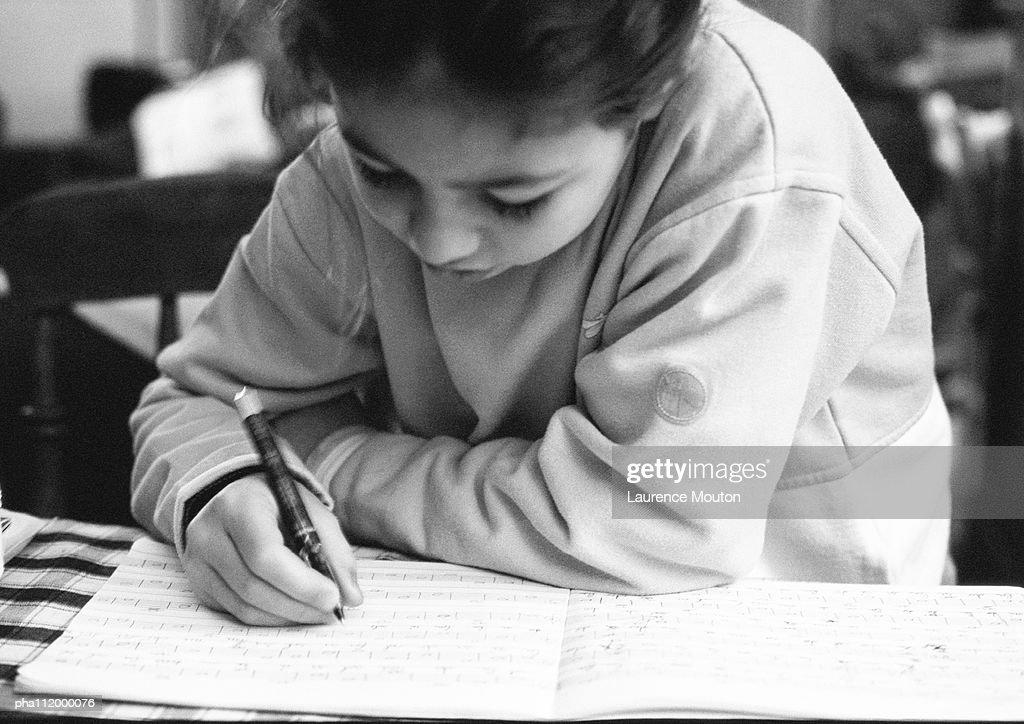 Boy bending head over notebook, writing, close-up : Stockfoto