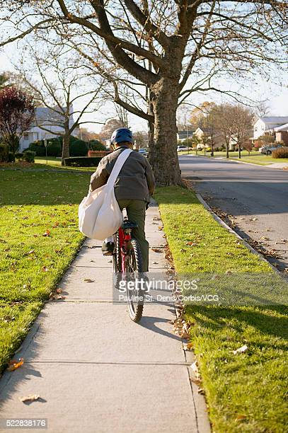 Boy bicycling along his paper route