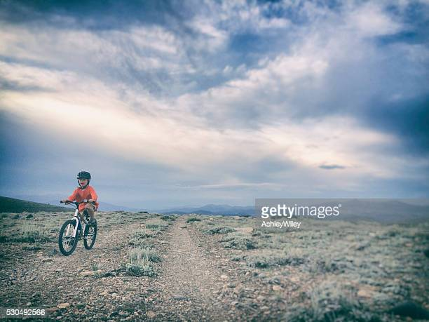Boy bike riding during a summer storm on deserted road