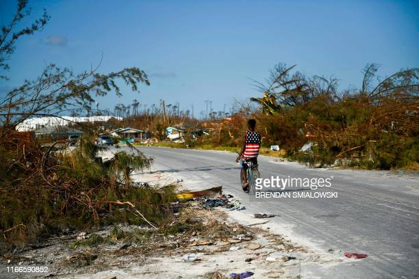 A boy bikes past destroyed trees in the Mudd neighbourhood in Marsh Harbour Great Abaco on September 7 in the aftermath of Hurricane Dorian Bahamians...
