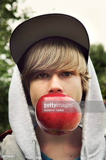 Boy biting a very big apple