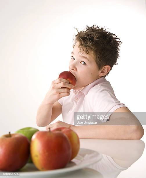 A boy biting into a red apple