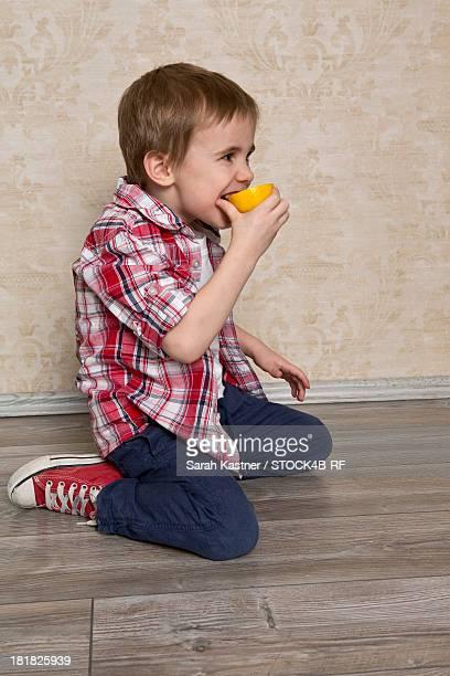Boy biting into lemon