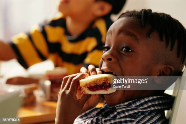 boy biting into sandwich - peanut butter and jelly sandwich stock pictures, royalty-free photos & images