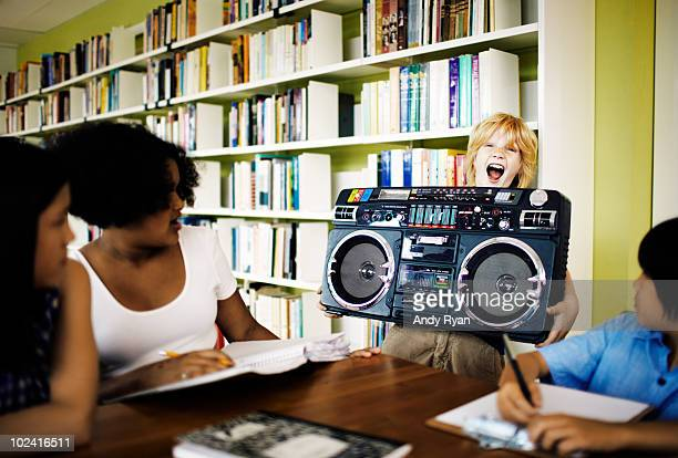 Boy blaring boombox in library