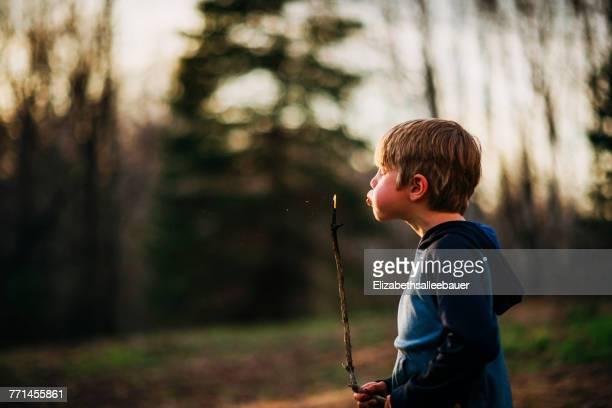 Boy blowing a smoking stick