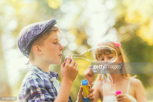 boy blowing a soap sud with girl in the background - spring flowing water stock pictures, royalty-free photos & images