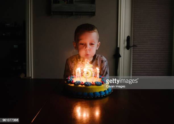 boy blowing birthday candles on table at home - 吹く ストックフォトと画像