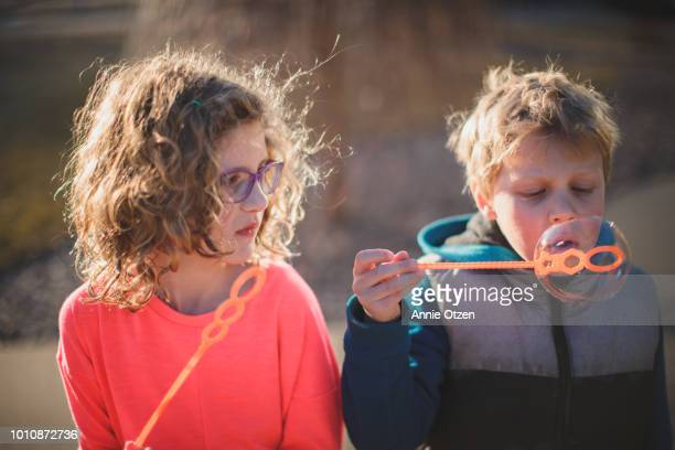 Boy Blowing Bubble While Girl Watches