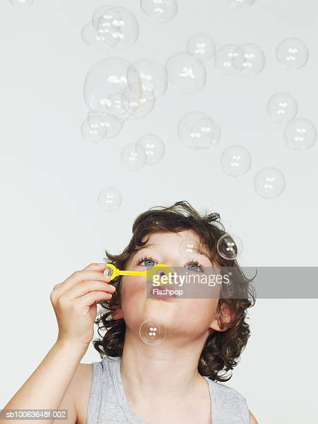 Boy (6-7) blowing bubbles, close-up
