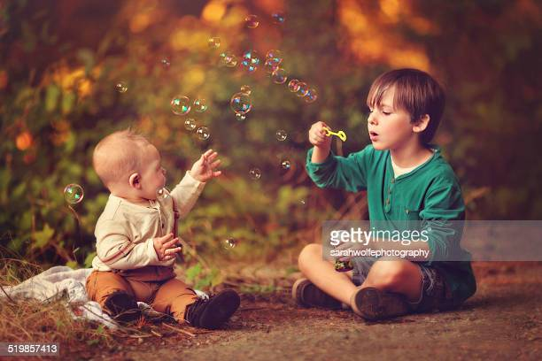 Boy blowing bubbles for a baby