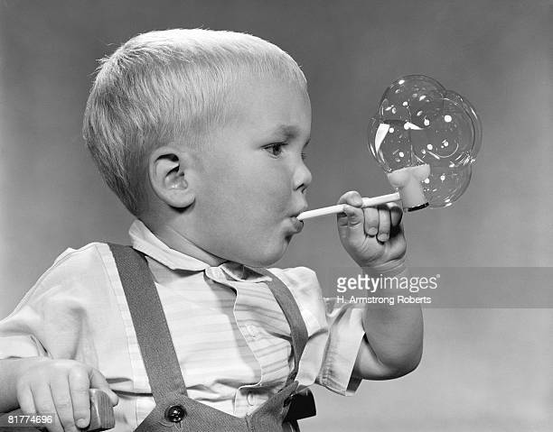 Boy blowing bubbles from pipe, profile.