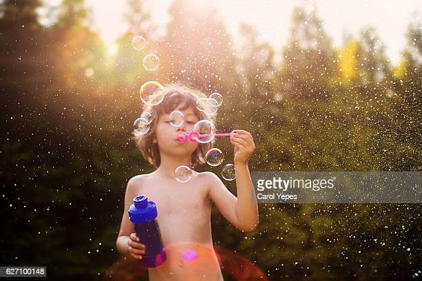 boy(8) blowing bubbles outdoor