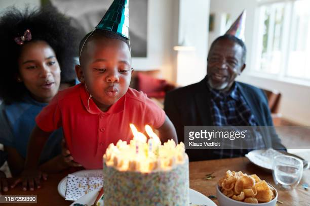 boy blowing candles on birthday cake at home - life events stock pictures, royalty-free photos & images