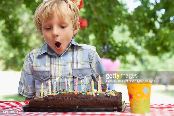 Boy blowing candles on birthday cake