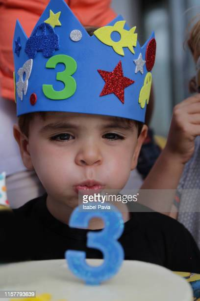 boy blowing candles on his cake at his third birthday - happybirthdaycrown stock pictures, royalty-free photos & images