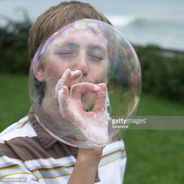 Boy (11-13) blowing large soap bubble