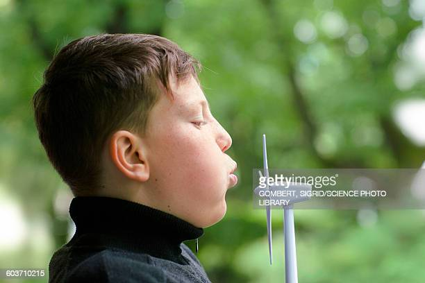 Boy blowing miniature wind turbine