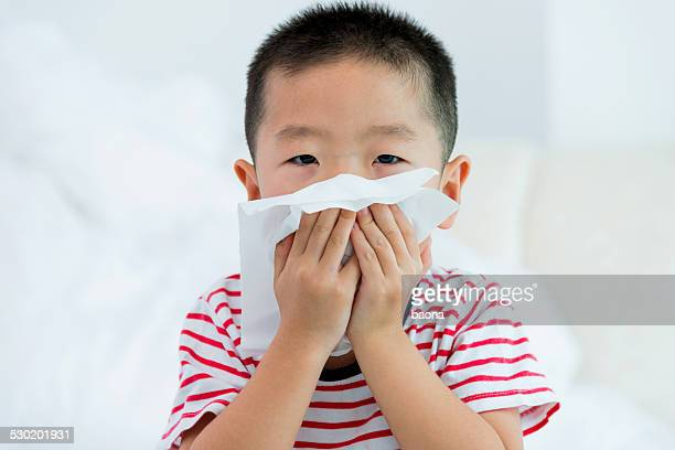 boy blowing nose