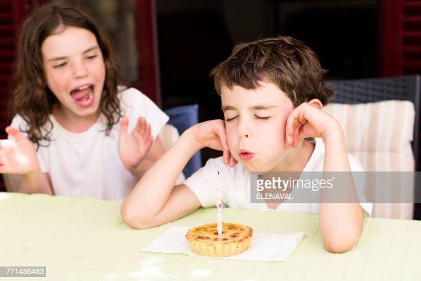 Boy blowing out birthday candle, his sister sitting next to him clapping