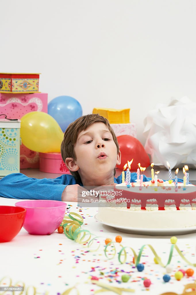 Boy Blowing Out Birthday Candles Stock Photo