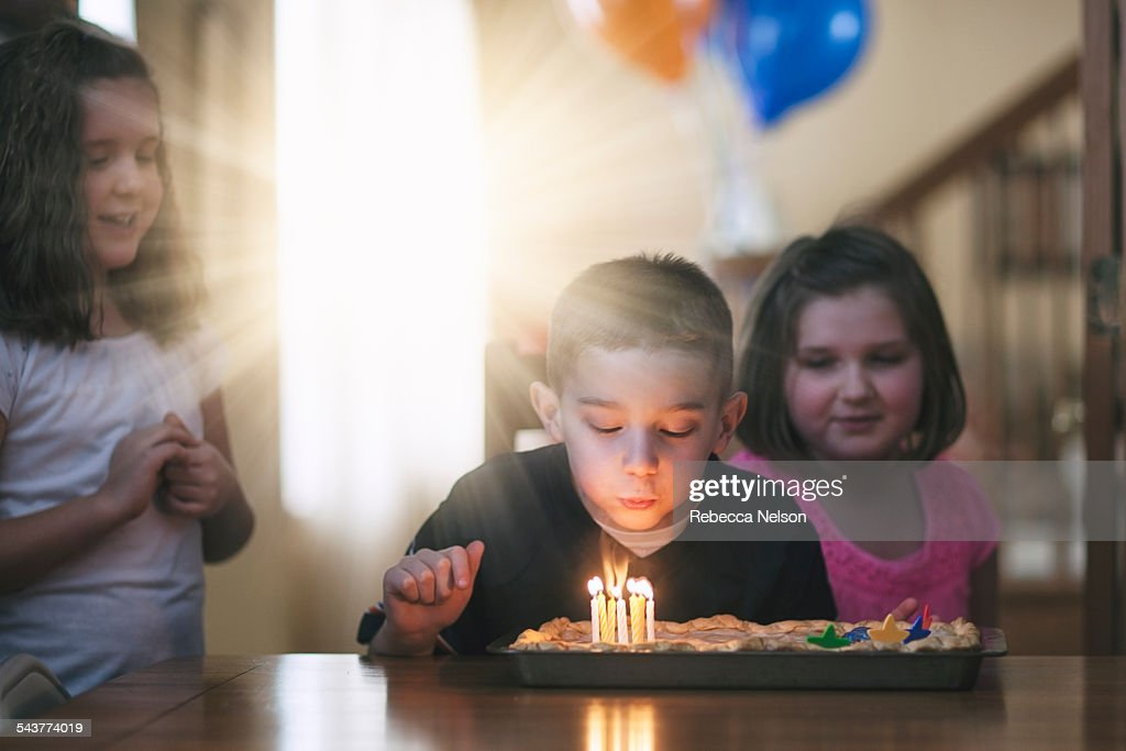 boy blowing out birthday candles : Stock Photo