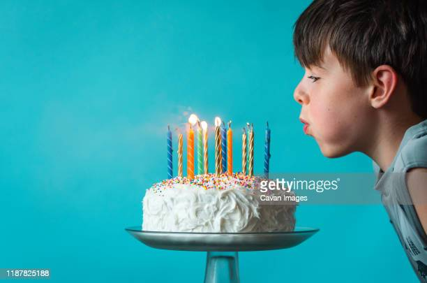 boy blowing out candles on a birthday cake against blue background. - happy birthday canada stock pictures, royalty-free photos & images