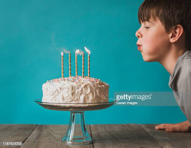 boy blowing out candles on a birthday cake against blue background. - birthday candle stock pictures, royalty-free photos & images