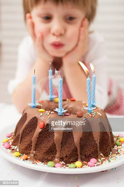 Boy (4-5) blowing out candles on birthday cake, close up