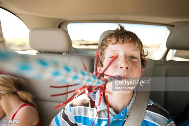 Boy blowing party blower in back seat of car