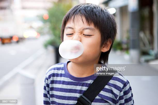 boy blowing up a bubble gum - far east stock photos and pictures