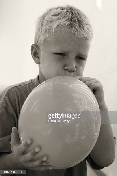 Boy blowing up balloon, close-up
