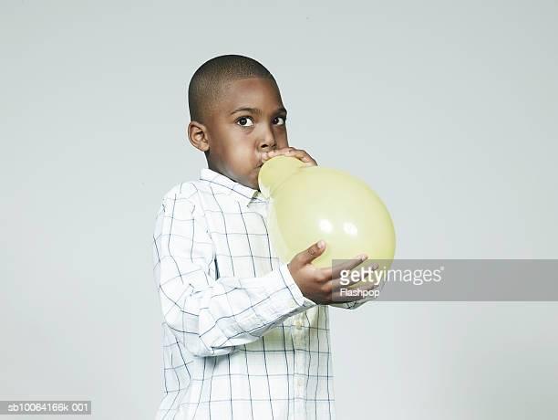Boy (6-7) blowing up balloon, looking away