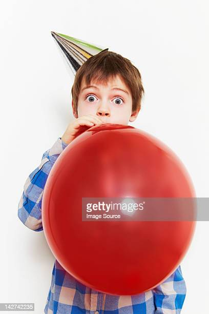 boy blowing up balloon - inflating stock pictures, royalty-free photos & images