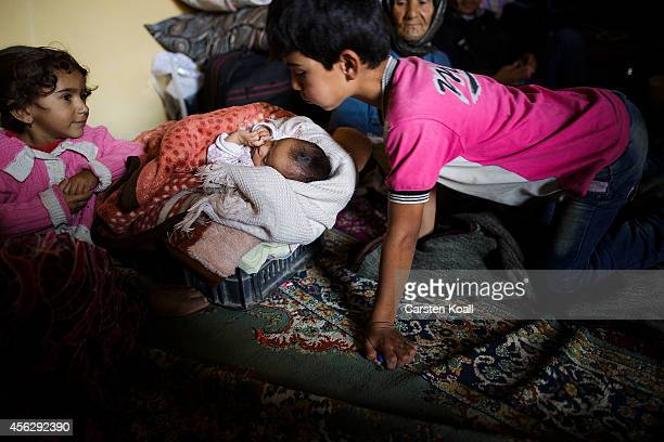 A boy blows at a baby sounded by his family in a temporary room in a refugee camp after crossing from Syria into Turkey in Suruc September 28 2014...