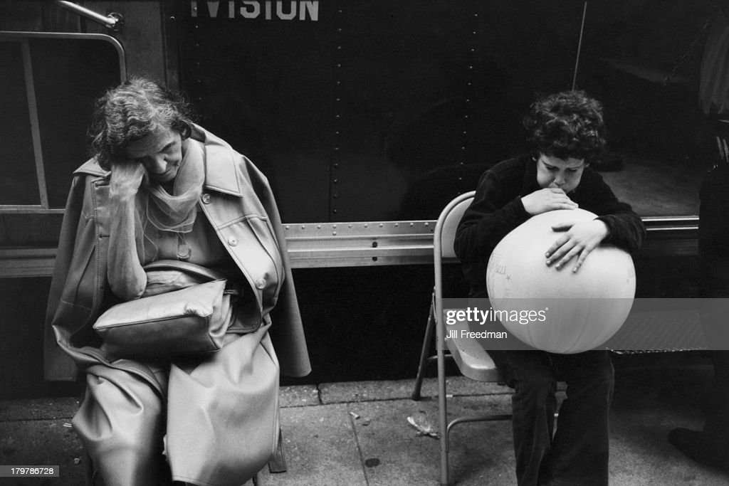 A boy blows up a large balloon next to a sleeping elderly woman, Lower Manhattan, New York City, 1979.