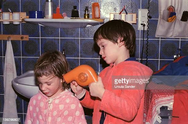 boy blows-dry hair of his sister - broer stockfoto's en -beelden
