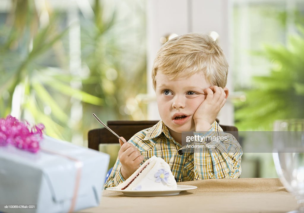 Boy (2-3 years) bored in front of cake and gifts : Foto stock