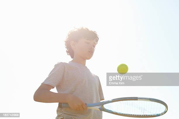 boy bouncing ball on tennis racket - racquet stock pictures, royalty-free photos & images