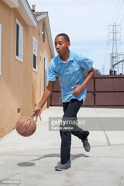 Boy bouncing basketball in yard