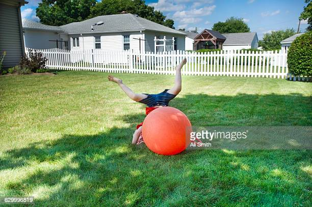 boy bouncing on orange ball - bouncing ball stock photos and pictures