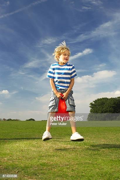 boy bouncing on space hopper