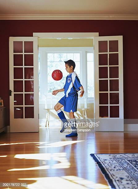 Boy (10-12) bouncing soccer ball on knee in living room of house