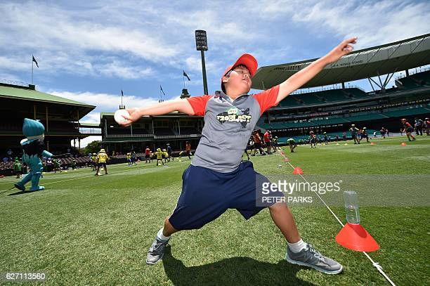 A boy bowls a ball as schoolchildren attempt to set a Guinness World Record for the Largest Cricket Lesson at the Sydney Cricket Ground on December 2...